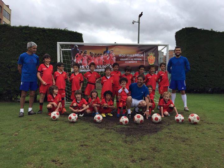 Julián Marcos, agachado, con los niños de la escuela de fútbol del Mallorca en Bogotá.