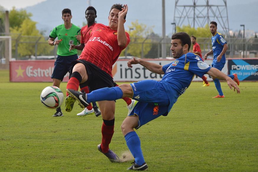 Pepe Bernal lucha un balón ante la presión de un rival (Foto: Fútbol Balear).