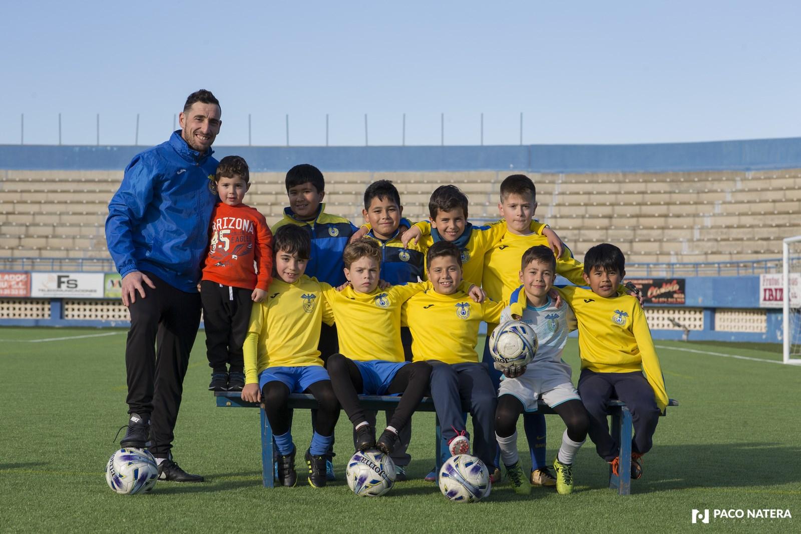 Ramiro es el entrenador del benjamín del Rápid, equipo con el que posa en Can Misses.